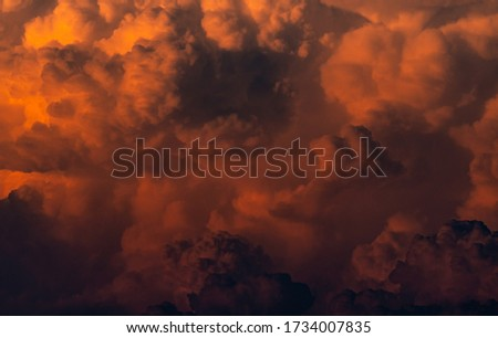 Red, orange fluffy clouds on sunset sky background. Art picture of orange clouds texture. Beautiful pattern of clouds. Dark and horror scene of sky. Beauty in nature. Powerful and spiritual scene.