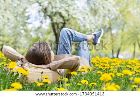 Relaxing woman lying on spring blooming meadow. Girl resting in summer park. Enjoy life, having fun, leisure, relaxation, springtime, lifestyle concept Royalty-Free Stock Photo #1734051413