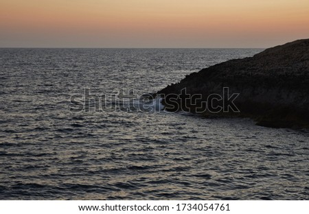 A beautiful picture of a reddish sunset by the Maltese coastline.