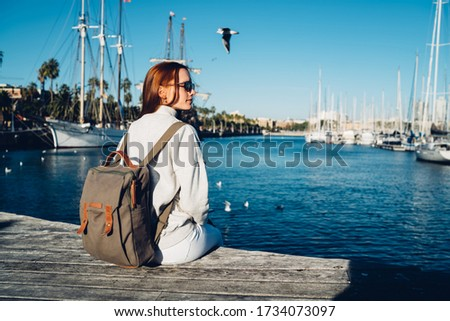 Young Caucasian female hipster tourist enjoying free day for promenade in harbor taking rest after walking near water dock, attractive red hair traveler recreating before voyage trip from dock Royalty-Free Stock Photo #1734073097