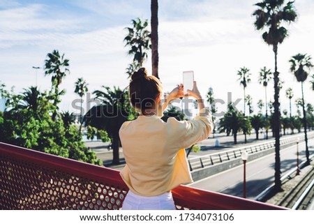 Back view of millennial female blogger using mobile application for clicking pictures via smartphone with blank screen for advertising of travel website, cellphone copy space with publicity area