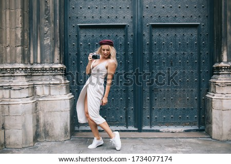 Happy Caucasian woman with retro camera having fun in historic center enjoying travel vacations for practicing photo skills, joyful youngster with old fashioned technology dancing in freestyle