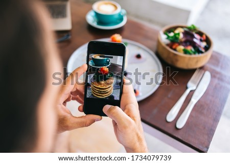 Cropped image of male influencer making photo of food for social networks via smartphone camera. guy blogger holding mobile phone taking picture of flatlay tasty pancakes stack on brunch in cafe