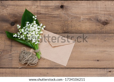 A bouquet of lilies of the valley tied with twine next to a letter envelope on a wooden background #1734106211