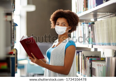 education, high school, university, learning and people concept - african american student girl wearing face protective medical mask for protection from virus disease reading book at library #1734106478