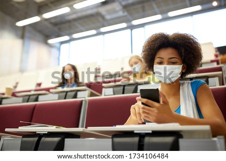 education, healthcare and pandemic concept - african student girl wearing face protective medical mask for protection from virus disease with smartphone at lecture Royalty-Free Stock Photo #1734106484