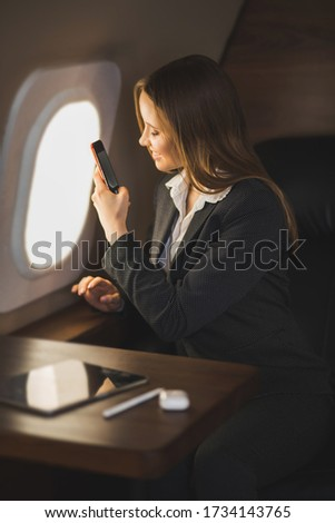 Happy attractive caucasian businesswoman traveling by private jet. Charming smiling lady sitting by aircraft window and taking photos of sky on her smartphone, enjoying flying first class.