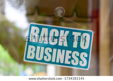 "Close-up on a blue closed sign in the window of a shop displaying the message ""Back to business"". #1734181145"