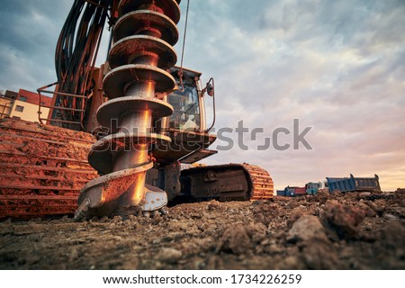 Building activity on contruction site. Close-up view of drilling machine against trucks.   Royalty-Free Stock Photo #1734226259