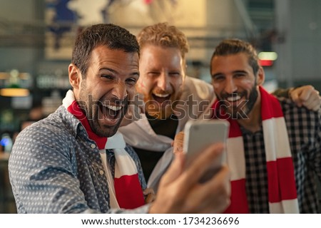 Excited men watching football in streaming on smartphone. Football fans watching game on phone and celebrating victory score at pub. Happy supporters cheering and exulting after winning an online bet. #1734236696