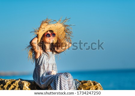 Little girl sunbathing, enjoying the sun and fresh sea air. She raised her face to the sun, sitting on the rocks by the sea. Sunglasses, beach hat, striped dress. #1734247250