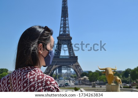 Young French woman with a cloth face mask photographed in front of the Eiffel Tower in Paris, France, during the Coronavirus pandemic. COVID-19 epidemic. Virus protection concept. #1734263834