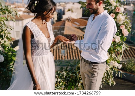 Mixed-race wedding couple - African-American bride and Caucasian groom. Groom puts a ring on brides finger. Destination fine-art wedding in Florence, Italy. Wedding ceremony on the roof #1734266759