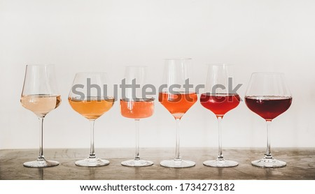 Various shades of Rose wine in stemmed glasses placed in line from light to dark colour on concrete table, white wall background behind. Wine bar, wine shop, wine tasting concept #1734273182