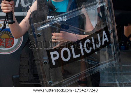 a child holds a police protective shield while training protection