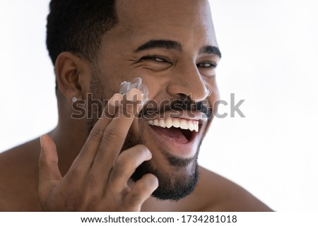Close up portrait of happy young african American man apply moisturizing face cream for healthy glowing skin, smiling millennial biracial male use nourishing facial balm, skincare, hygiene concept Royalty-Free Stock Photo #1734281018