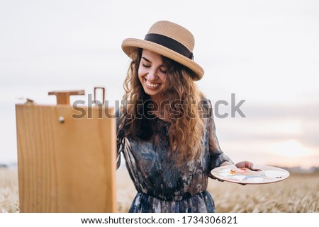 Portrait of smiling female artist with curly hair in hat. Girl draws a picture of a landscape in a wheat field.