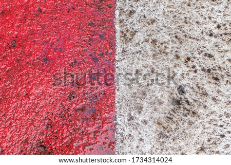 abstract background of red and white markings for fire fighting equipment on wet pavement after a rain close up