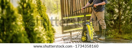 Unrecognizable man cleaning a wooden gate with a power washer. High pressure water cleaner used to DIY repair garden gate. Web banner. Royalty-Free Stock Photo #1734358160