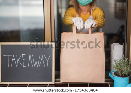 Young woman preparing takeaway organic food inside restaurant during Coronavirus outbreak time - Worker inside kitchen cooking food for online delivery service - Focus on hands #1734363404
