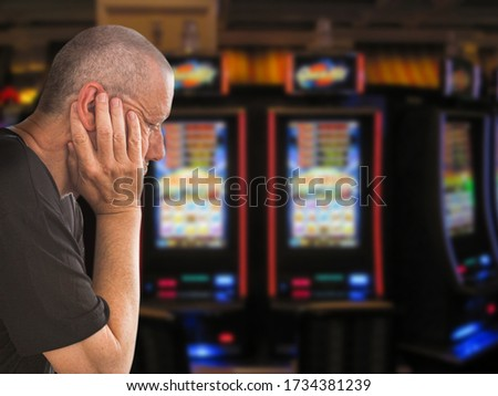 Sad and depressed caucasian man sitting with his hands on his head in front of rows of casino slot machines. Gambling addiction theme image.  Close up portrait. Royalty-Free Stock Photo #1734381239