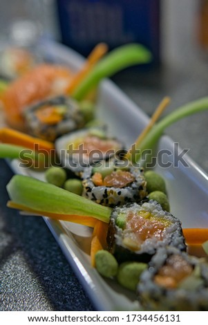 Freshly prepared homemade collection of Sushi variety nicely decorated on a white plattern. The picture shows one of the most popular Sushi dishes - a cut Salmon maki roll.