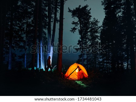 Bearded Man silhouette is walking against tree trunk in the night forest near glowing orange tent in the mountains. #1734481043