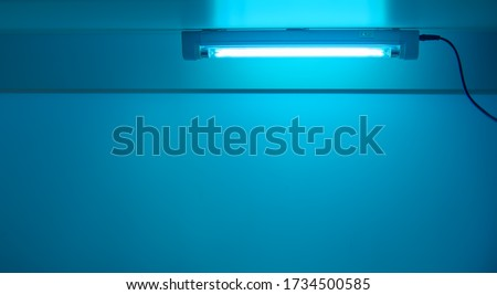 Blue light from ultraviolet lamp. UV lamp sterilization of air and surfaces. Coronavirus epidemic prevention concept. Copy space #1734500585