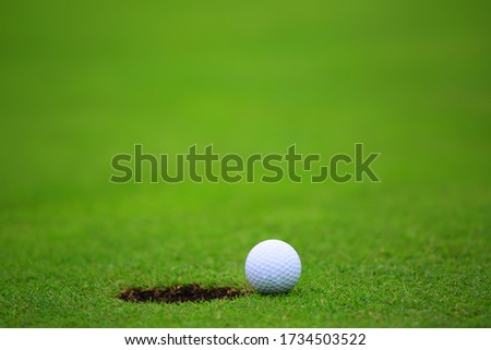 Golf ball close to hole, on lip of cup on green of golf course background with copy space for text banner #1734503522