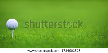 Golf ball on tee on green grass of golf course background, backgrounds for banner foth copy space for text #1734503525