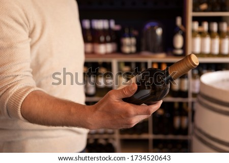 A man holding  a wine bottle in a liquor wine shop. Choosing the right wine from all the variations of wine bottles on the shelves in the bokeh background. #1734520643