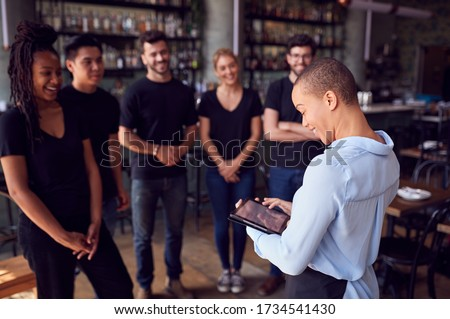 Female Restaurant Manager With Digital Tablet Giving Team Talk To Waiting Staff Royalty-Free Stock Photo #1734541430