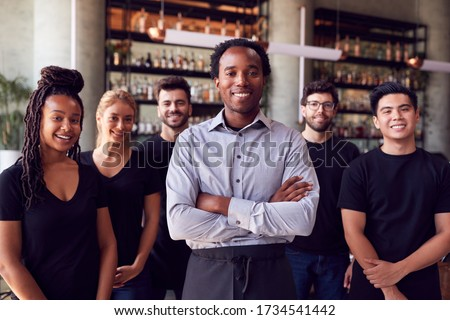 Portrait Of Male Owner Of Restaurant Bar With Team Of Waiting Staff Standing By Counter Royalty-Free Stock Photo #1734541442