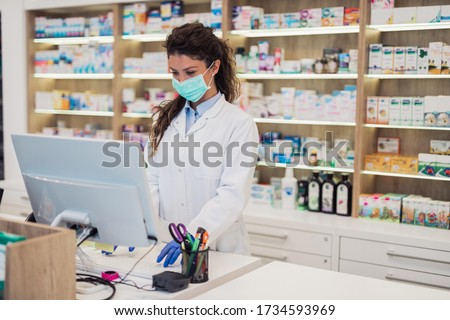 Female pharmacist with protective mask on her face working at pharmacy. Medical healthcare concept. Royalty-Free Stock Photo #1734593969