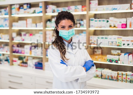 Female pharmacist with protective mask on her face working at pharmacy. Medical healthcare concept. Royalty-Free Stock Photo #1734593972