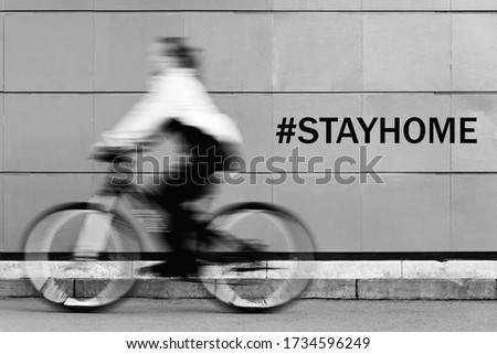 A man in blurry focus rides a Bicycle with the words stay at home during quarantine on the wall. Athletic girl engaged in Cycling
