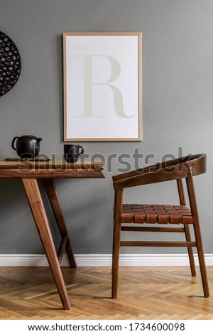 Stylish scandinavian dining room interior with mock up poster frame, wooden table, furniture, tea pot , decoration and elegant accessories in modern home decor.