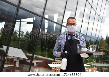 Waiter cleaning the table with Disinfectant Spray in a restaurant wearing protective medical mask and gloves new normal concept Royalty-Free Stock Photo #1734653804