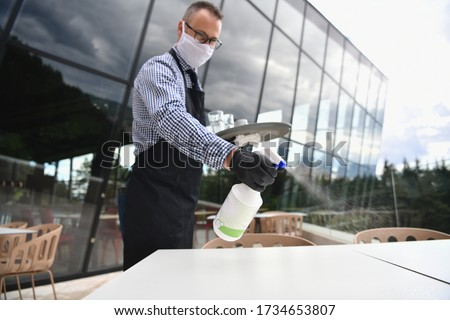 Waiter cleaning the table with Disinfectant Spray in a restaurant wearing protective medical mask and gloves new normal concept #1734653807