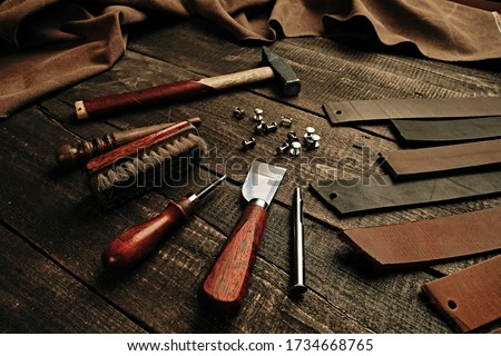 Leather samples and set crafting DIY tools on wooden table background texture. Leather craftmans work desk. Copy space, maintenance concept. Belt production. Royalty-Free Stock Photo #1734668765