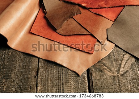 Natural color leather. Materials for leather craft. Copy space. Multi colored leather in rolls. Handmade craft. Different samples of leather on wooden table Royalty-Free Stock Photo #1734668783