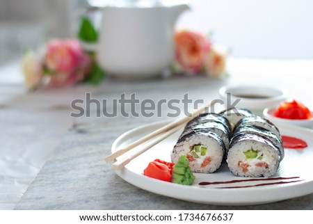 Sushi Rolls asian food stylish beautiful close up picture. Tasty delishes meals with rice and seafood on the white plate and light gray table with ginger and wasabi with Blurred background, copy space
