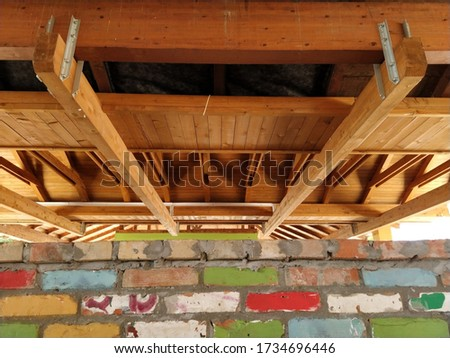 Wooden construction - roof truss made of beams. Rafters and support beams made of fresh wood. Downstairs brick wall with multi-colored painted bricks #1734696446