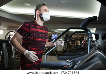 Young man running on treadmill in indoor gym,wearing protective face mask & rubber latex gloves,COVID-19 pandemic prevention of spread & transfer of Coronavirus,staying fit in lockdown concept in US #1734701594