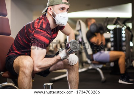 Young men working out wearing face mask & latex rubber gloves,performing bicep curl with dumbbells,COVID-19 pandemic social distancing rules while working out in reopened indoor gym,prevent & protect #1734703286