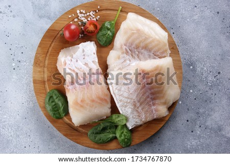 Seafood. Raw white fish, cod fillet on a wooden board with spinach, herbs, tomatoes and spices on a light grey background. Flatlay, top view. Background image, copy space