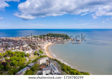 Aerial photo of the town centre of Scarborough in East Yorkshire in the UK showing the coastal beach and harbour with boats and the Scarborough Castle on a bright sunny summers day #1734780299