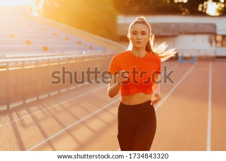 Young woman running during sunny morning on stadium track. Picture of young attractive fitness girl jogging. Athletic girl running.