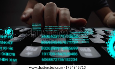Man working on laptop computer keyboard with graphic user interface GUI hologram showing concepts of big data science technology, digital network connection and computer programming algorithm. #1734945713