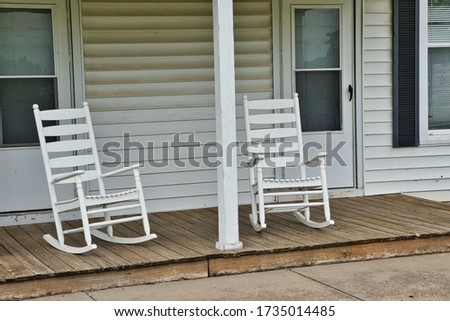 White rocking chairs on front porch. #1735014485